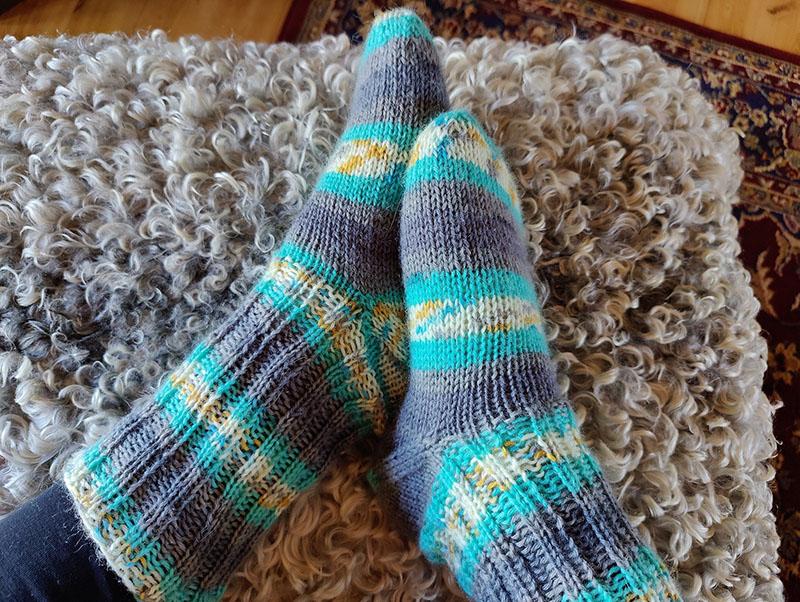 Två fötter med stickade raggsockor på. Raggsockorna är randiga i vitt, grått, gult och turkost.