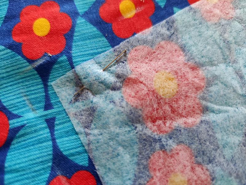 Bilden visar ett mörlblått tyg med turkosa blad och röda och gula blommor. Ovanpå tyget ligger en bit mönsterpapper fastnålat.