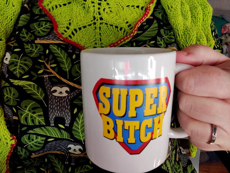 En bild där man ser min hand som håller en mugg med texten Super Bitch. Jag har en klänning med glada sengångare och gröna blad på, och en knallgrön stickad sjal i spetsmönster.