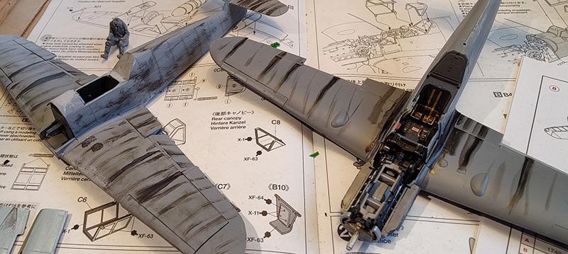 Bilden visar två modellflygplan i ett tidigt stadie. De är gråa med några målade svarta partier. De ligger på en ritning.