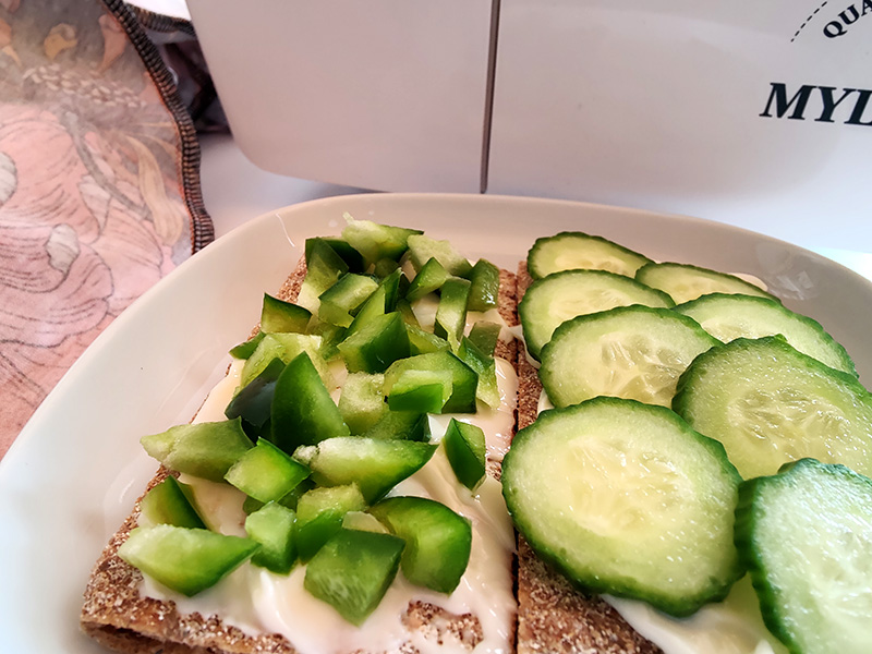 Bilden visar två knäckemackor med gurka och grön paprika. Bakom mackorna skymtar en overlockmaskin och en klänning jag håller på med.
