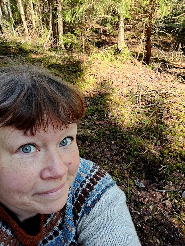 En bild på mig där jag sitter på huk i skogen och ser glad ut. Skogen är härlig!