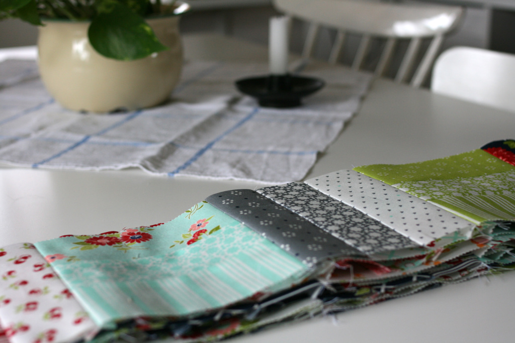 På ett vitt köksbord ligger en trave ihopsydda tyglappar i olika färger.