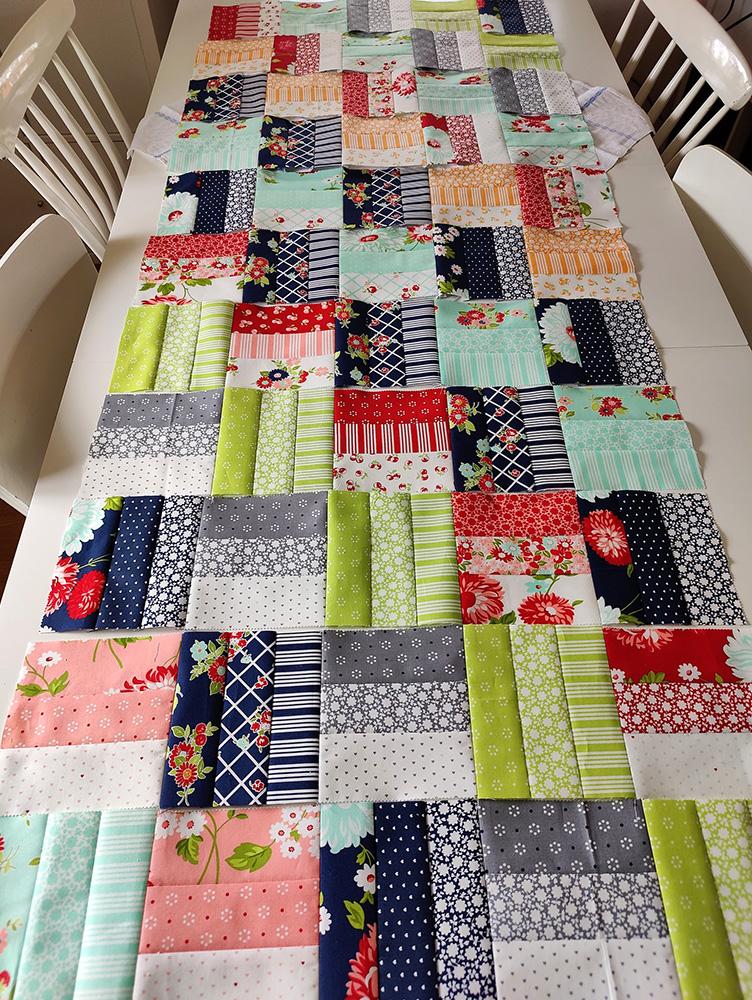 Bilden visar ett köksbord på vilket det ligger rader med lapptäcksrutor i olika färger: rött, blått, grönt, rosa, mintgrönt, grått.