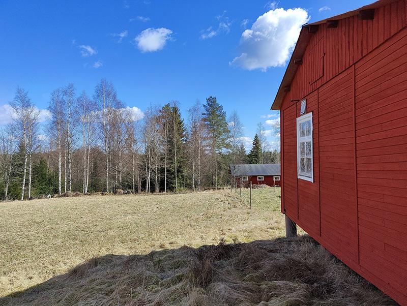 En liten röd byggnad med ett vitt fönster till höger i bild. Till vänster en åker. I bakgrunden skogen och en liten röd stuga.