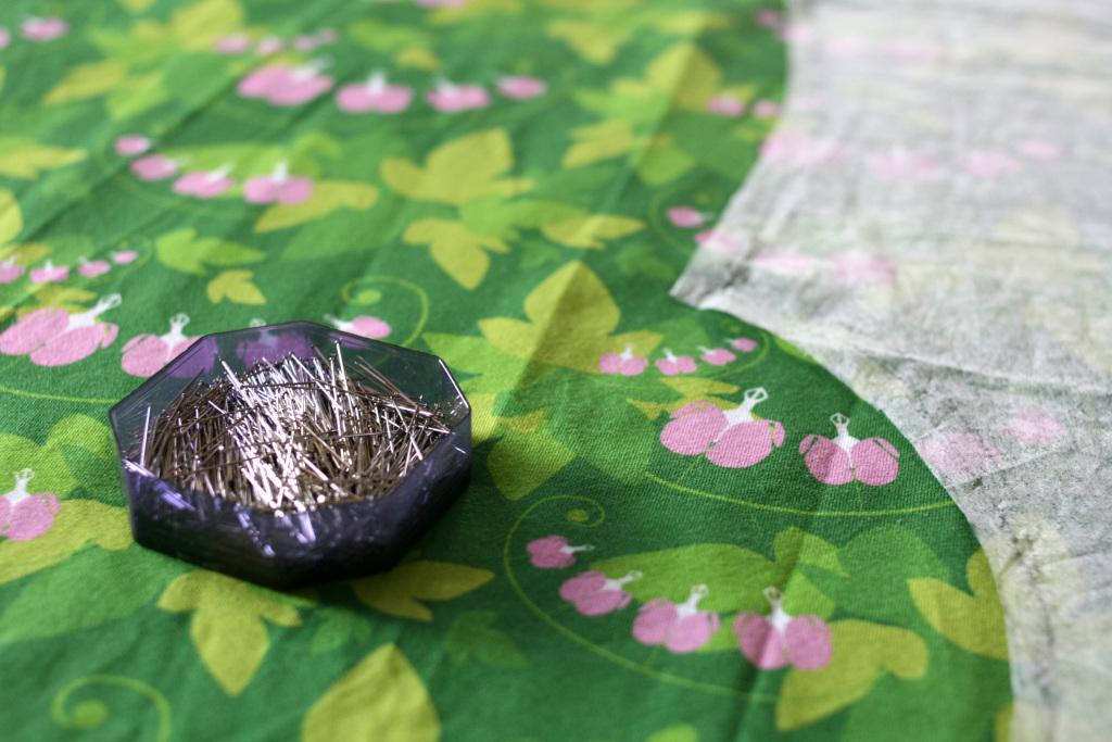 En ask med nålar på ett grönt tyg med rosa löjtnantshjärtan på. Man skymtar också en del av ett mönster, fastnålat på tyget.