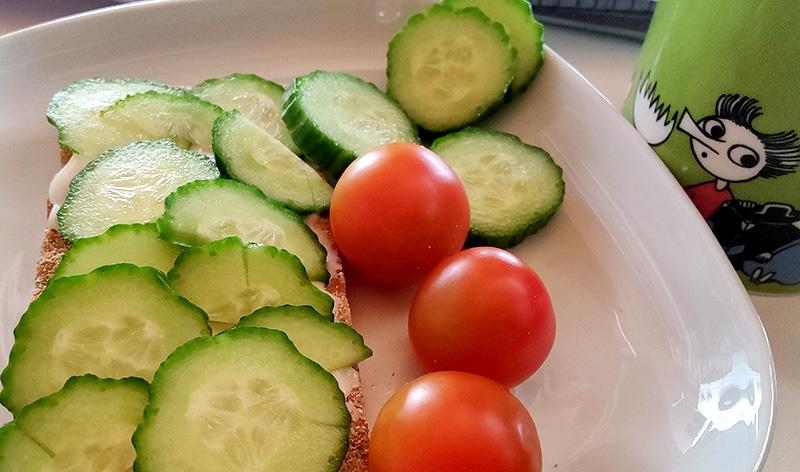 Bilden visar en knäckemacka med en hög gurkskivor på, intill mackan ligger några körsbärstomater.