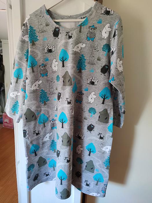 En klänning hänger på en galge. Klänningen är grå med muminfirgurer i vitt, turkost, svart och grått.