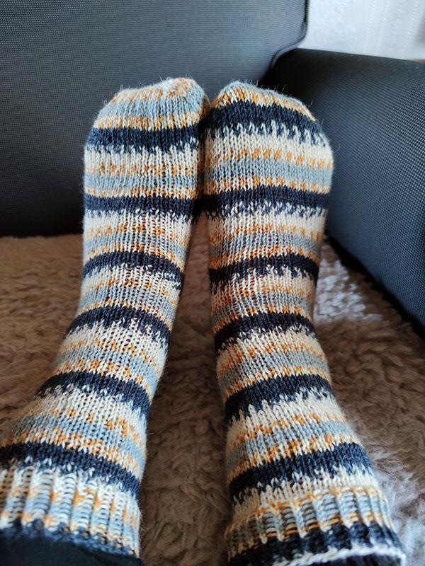 Två fötter med stickade raggsockor på. Raggsockorna är randiga i vitt, grått, gult och svart.