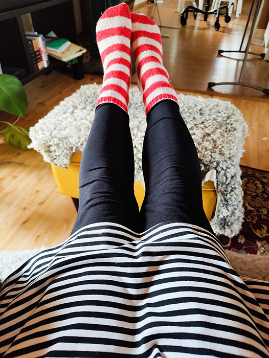 Jag sitter i en fåtölj och sträcker ut benen framför mig. På fötterna har jag röd och vitrandiga stickade strumpor och jag har en svart och vitrandig klänning på mig.