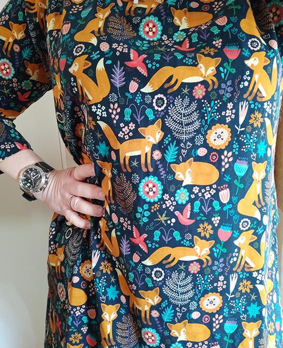 En klänning med orange rävar och färgglada blommor, fåglar och växter, på mörkblå botten.