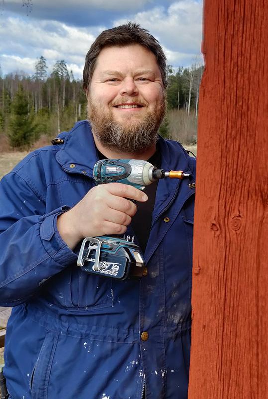 En bild på en leende Rickard, klädd i blått, som står vid en faluröd knut med en skruvdragare i handen.