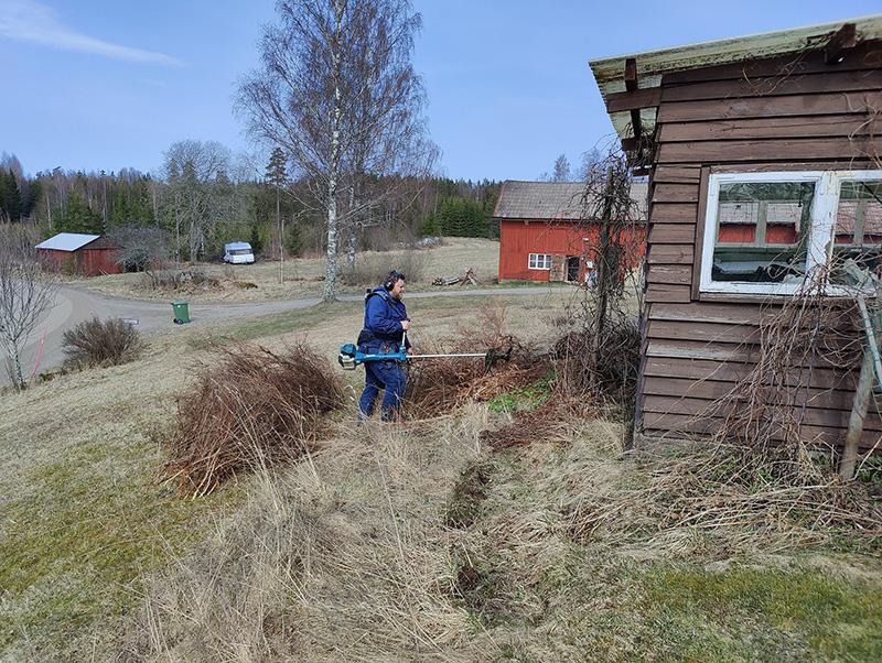 Bilden visar Rickard, klädd i blått, med en röjsåg. Han kapar ner en buske intill vårt lilla uterum i brunmålat trä. I bakgrunden ser man en del av ena ladan, den är röd. Man kan också se ett gammalt garage, en husvagn och bortom dem, en åker och sen skogen.