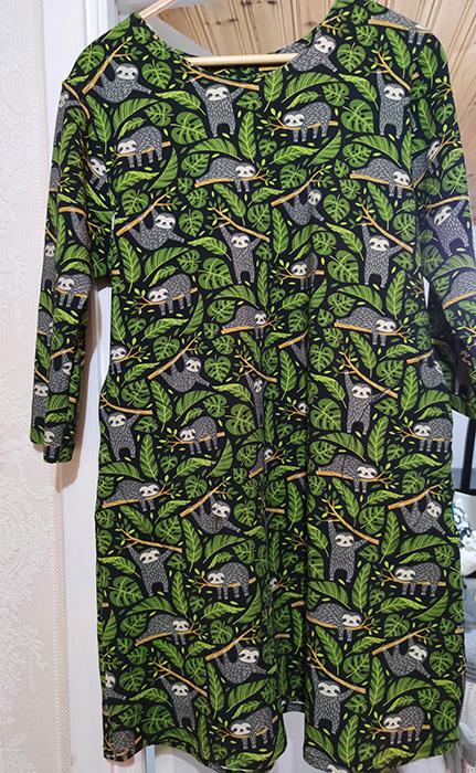 En klänning hänger på en galge. Klänningen har grå sengångare och gröna blad på en svart botten.