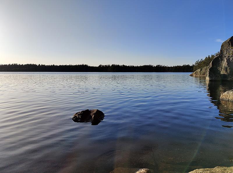 Utsikt över sjön. Solen blänker i vattnet, himlen är blå. Till höger skymtar några klipphällar.