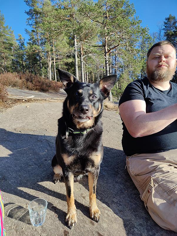 Qvick (svart hund) och Rickard (klädd i svart t-shirt och beige shorts) sitter bredvid varandra på en klipphäll, med tallskog i bakgrunden.