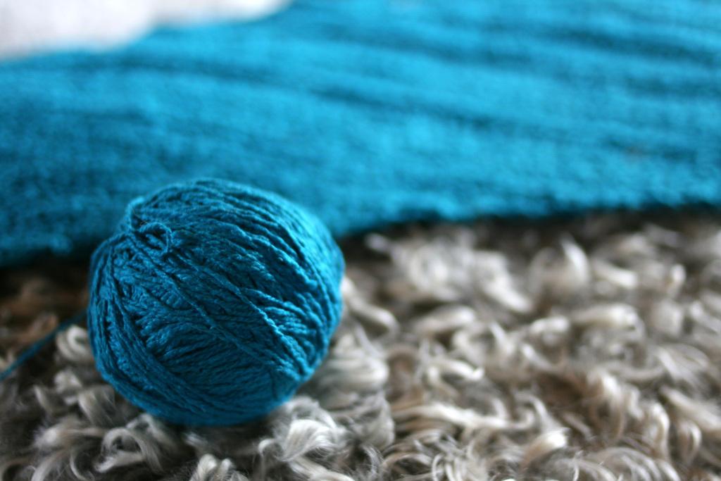 Närbild av ett turkost garnnystan på ett grått fårskinn.