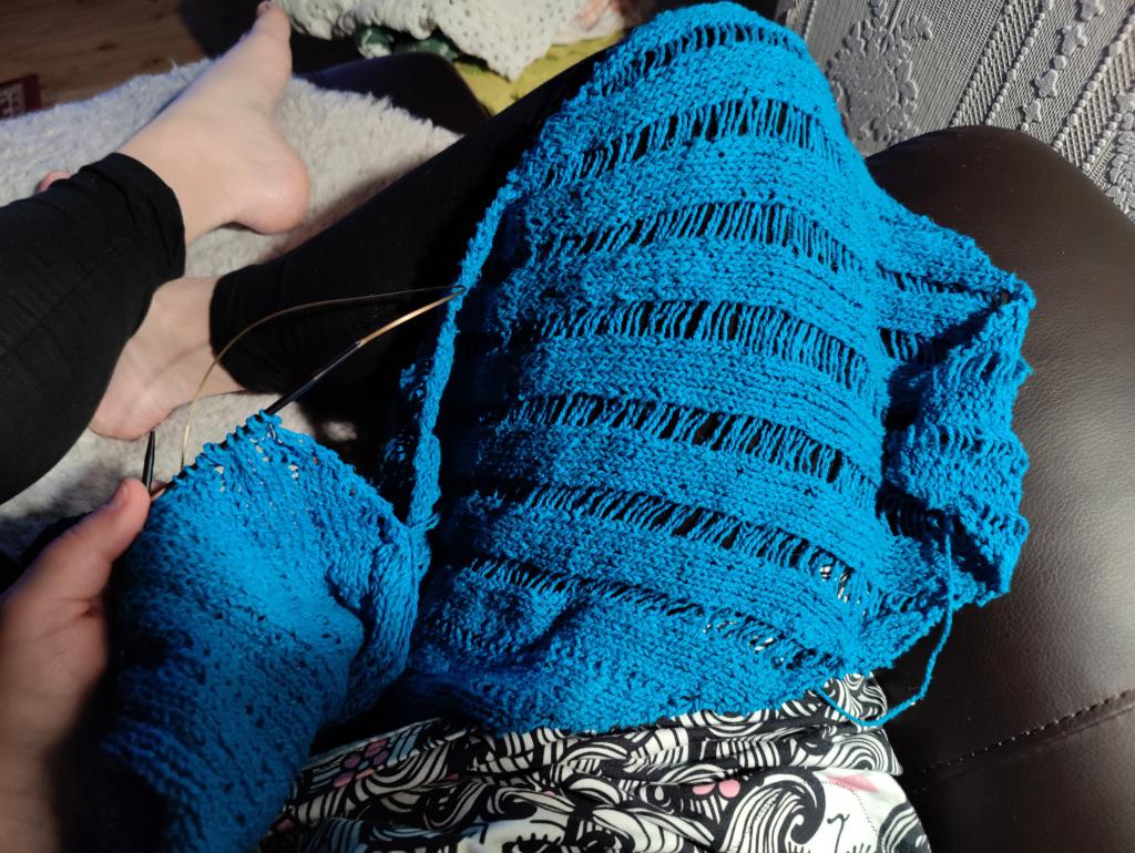 En mörkturkos stickning, en blivande sjal, draperad över mitt knä.