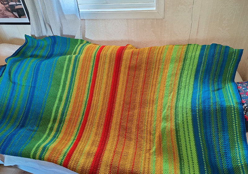 Bilden visar en randig, färgglad virkad filt i färgerna blå, turkos, ljusgrön, mörkgrön, gul, mörkgul, orange, röd.