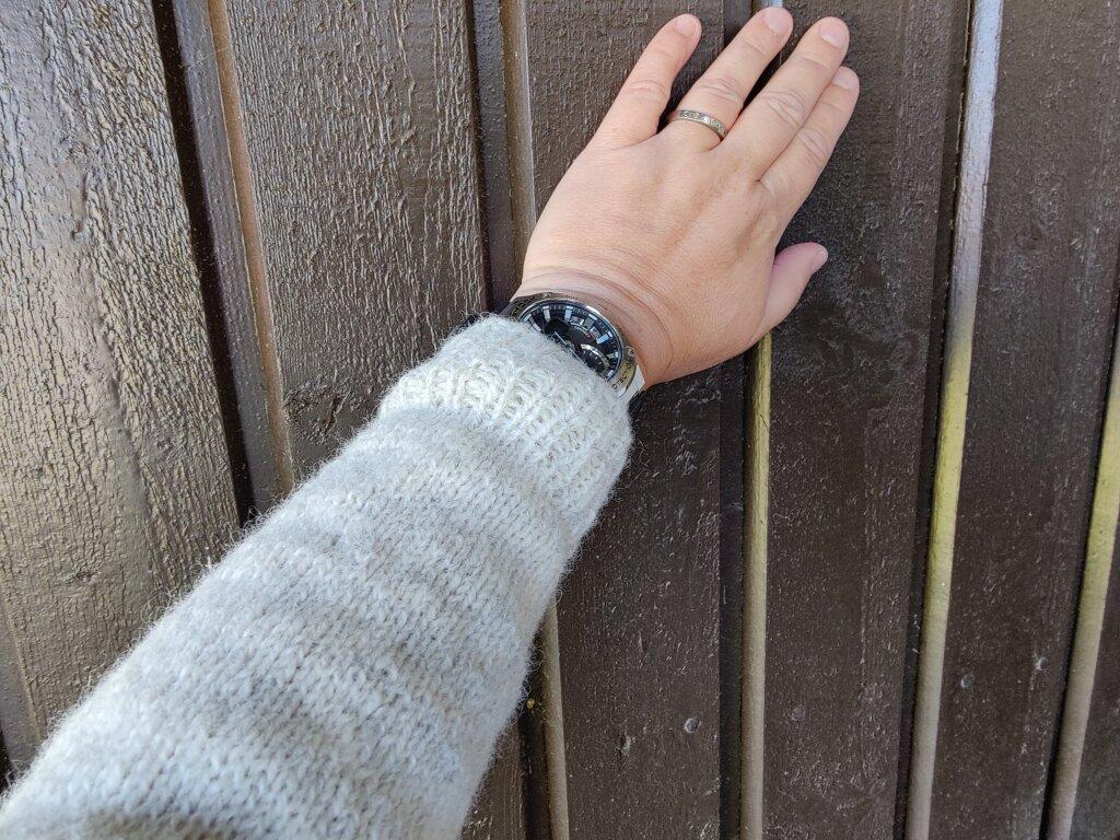 Bilden visar min arm, klädd i ljusgrå stickad tröja. Jag håller upp armen med handen mot en husvägg.