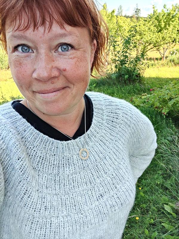 En selfie där jag har på mig den ljusgrå stickade tröjan. Jag har rött hår och blåa ögon och ser glad ut.