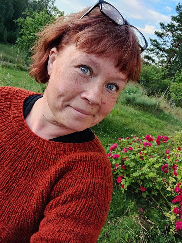 En selfie där jag bär en rostbrun stickad tröja och ler in i kameran.
